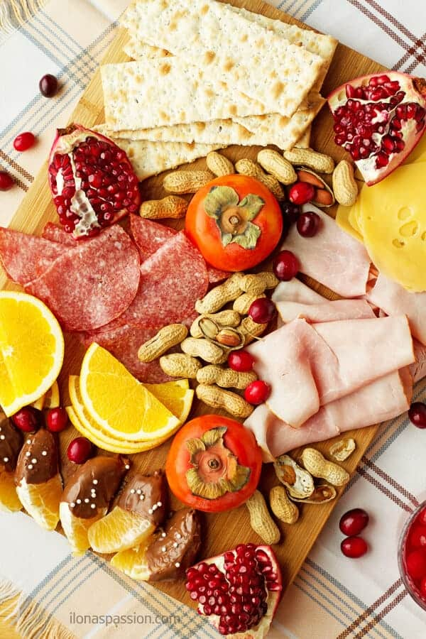 Winter appetizer platter including seasonal products including cranberries, oranges, cheese, persimmon, pomegranate, nuts, ham and salami by ilonaspassion.com I @ilonaspassion