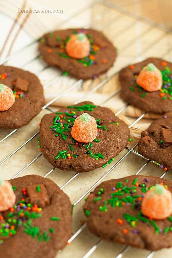Multiple chocolate chunk cookies decorated with green sprinkles and orange pumpkin sour candy.