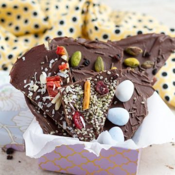 A gift idea basket of chocolate bark decorated with easter eggs, pretzels , cranberries and pistachios.