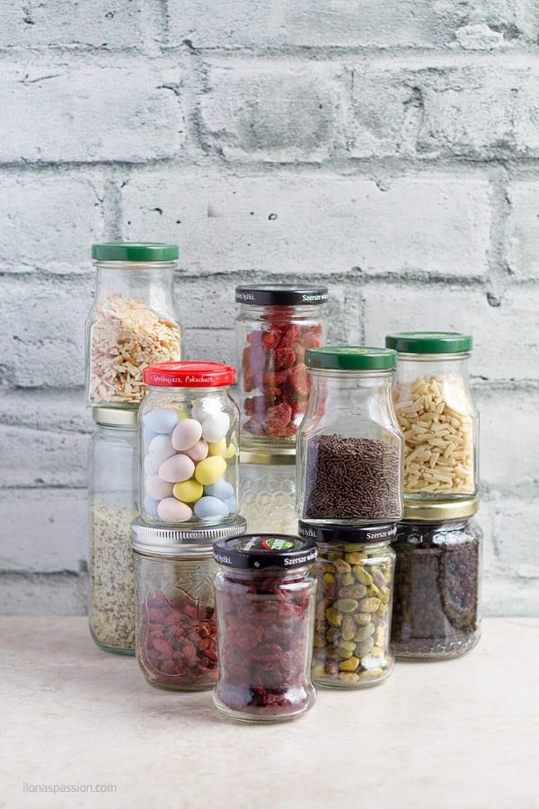 Jars with nuts, candies, hemp hearts, dried fruits and sprinkles.