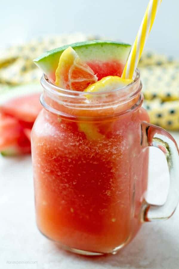 Blended watermelon slushie in a large glass with yellow straw and few pieces of the fruit wedges behind it.