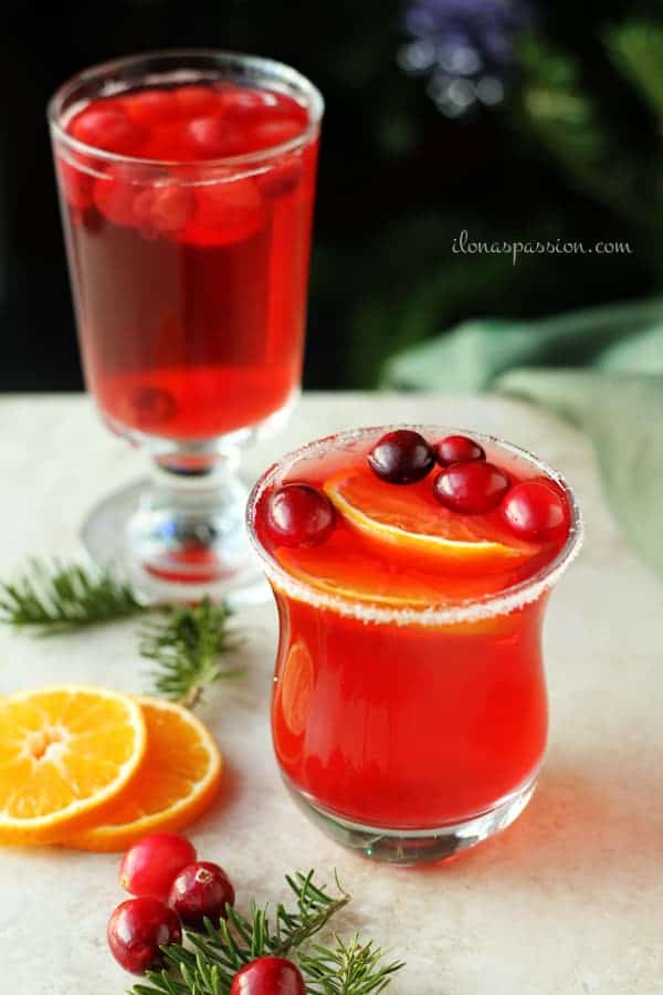 Cranberries in a glass of homemade drink and few slices of orange.