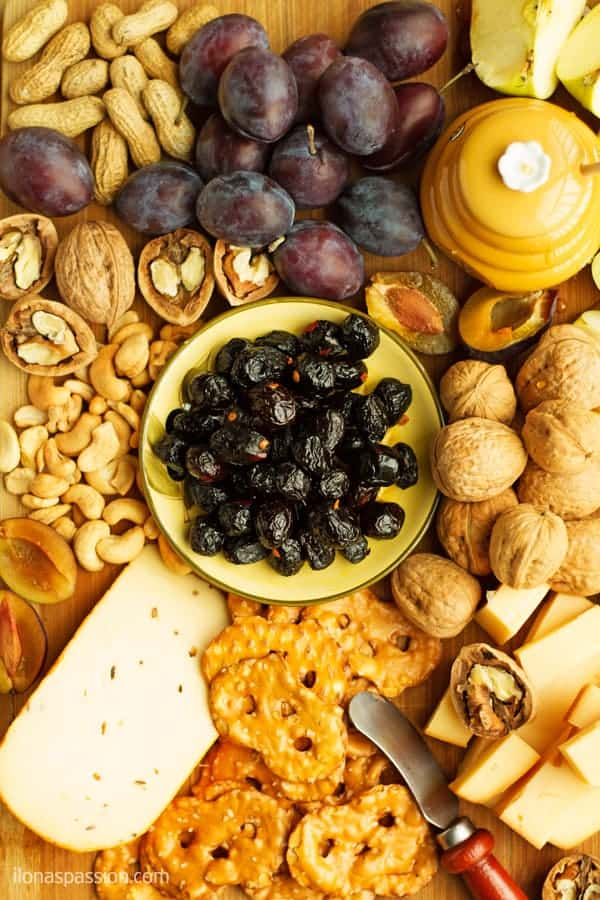 Fall fruit and cheese platter ideas to impress your guests at the party including gouda cheese, cashews, peanuts, walnuts and fruits like apples or pears.