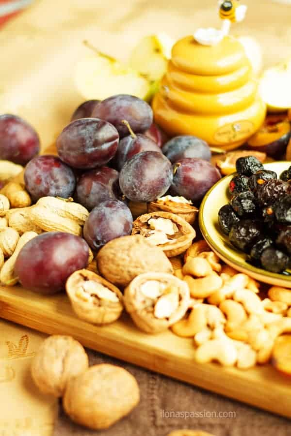 Cheese platter appetizer ideas with plums, apples and nuts.