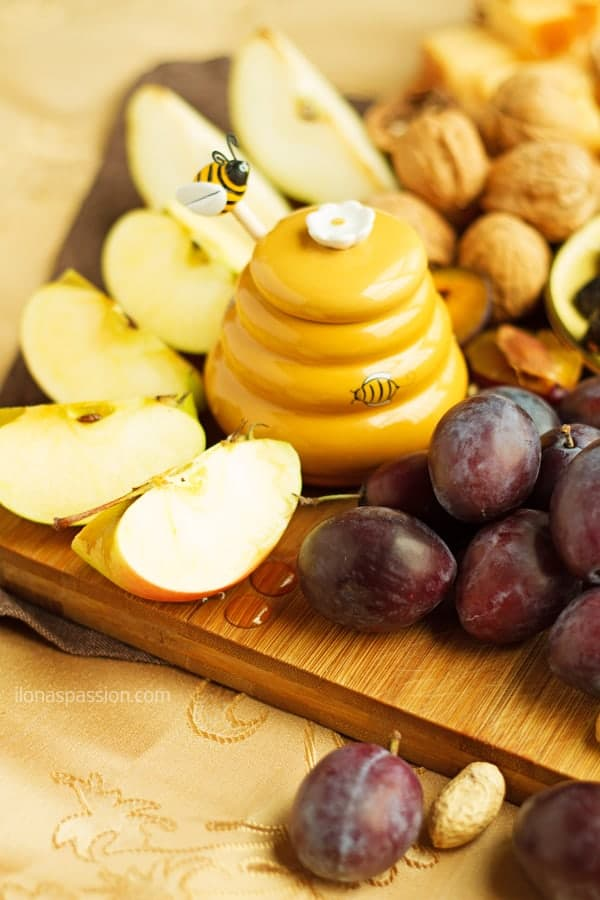Simple board for party including seasonal fall fruits like plums and apples topped with honey.