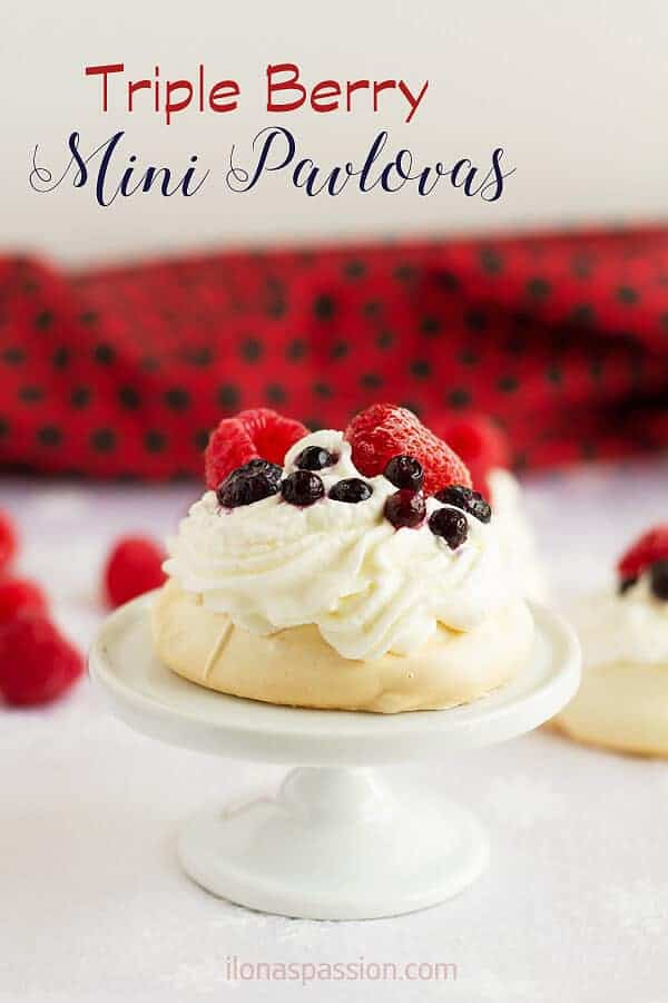 Delicate and elegant triple berry mini pavlovas recipe with whipped cream and raspberries, blueberries and strawberries. Perfect for any occasion! by ilonaspassion.com I @ilonaspassion