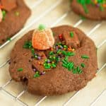 A close up photo of pumpkin patch chocolate chunk cookie decorated with sprinkles and 1 orange pumpkin candy patch.