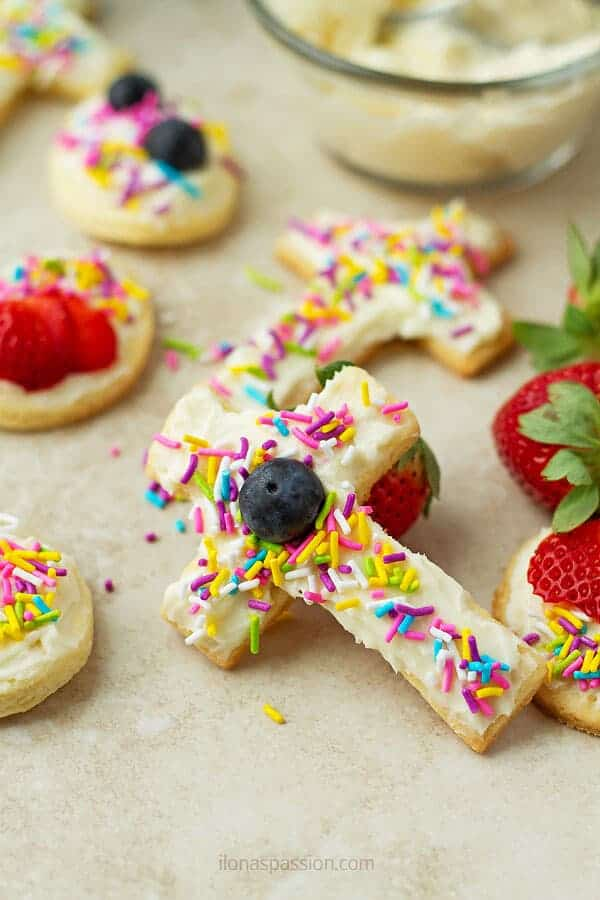 A cross shaped buttery cookie with blueberry, white frosting and sprinkles, some strawberries in the back and few other cookies.