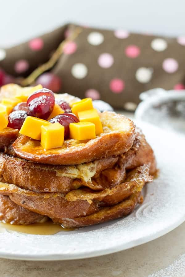 Challah French toast stacked on each other and topped with mango and grapes by ilonaspassion.com I @ilonaspassion