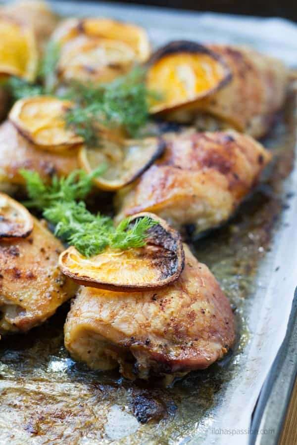 Sheet pan chicken pieces topped with lemon and orange slices by ilonaspassion.com I @ilonaspassion