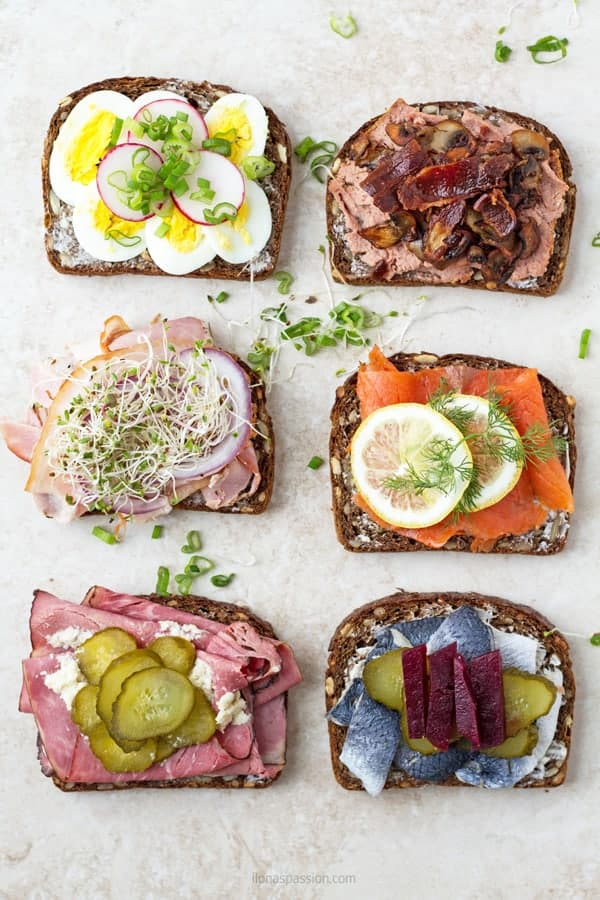 6 types of smorrebrod Danish sandwiches with liver pate, salmon, roll meat, herring, roast beef and egg. Decorated with lemon slices, radishes, pickles, micro greens and roasted beet.