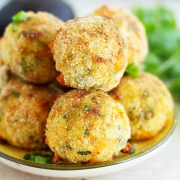 Stuck of arancini placed on a plate topped with green onion.