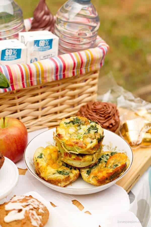 Egg muffins on a table as a picnic finger food with basket and bottle water.