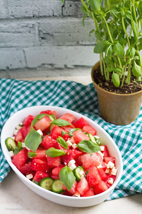 Watermelon salad with cucumber and fresh basil leaves.